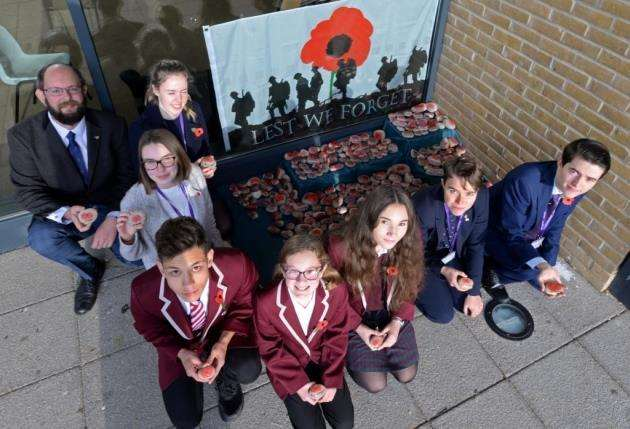 Birchwood School, Bishops Stortford. Pupils have created 308 poppy stones each with the name of a local soldier that lost his life in WW1 or WW2. Head of History Will Morton and pupils with the stones. Pic: Vikki Lince