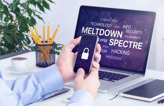 Meltdown and spectre vulnerability concept. Chipocalypse Meltdown and Spectre threat on laptop and smartphone screen.