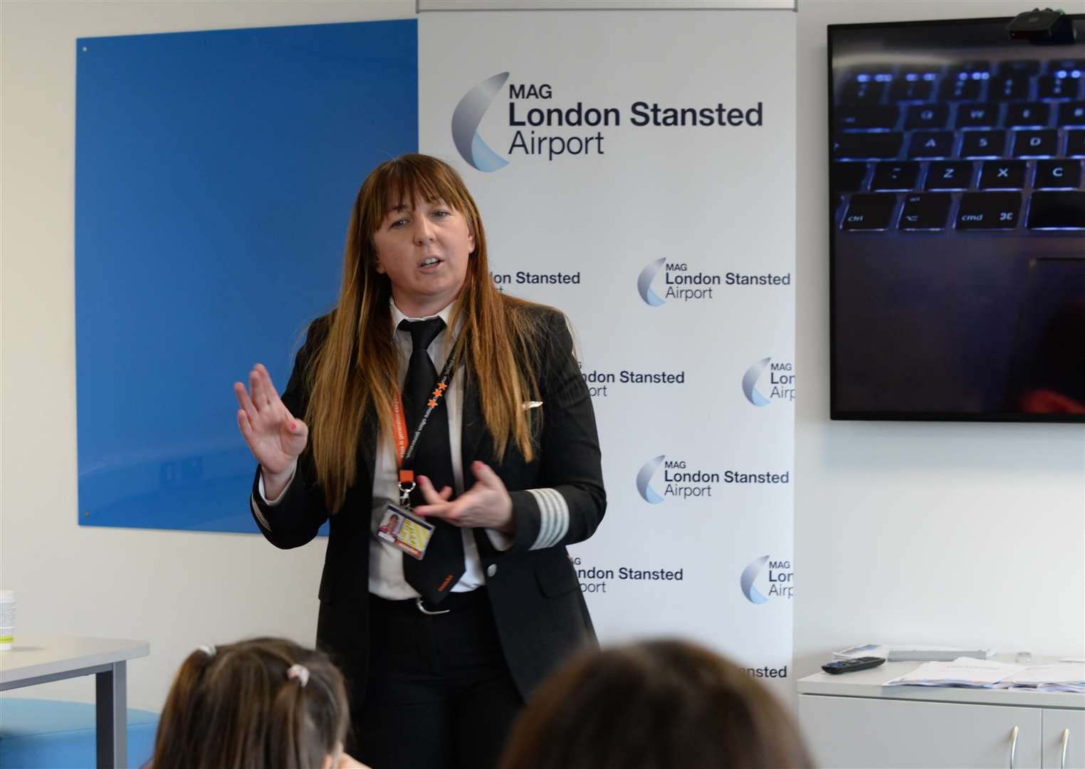 Stansted Airport College. Visit by Aviation Minister Baroness Liz Sugg in advance of International Womens Day. Speaking to Women involved in aviation, apprentices and pupils from Thaxted Primary School. .Easy Jet pilot Capt. Sarah Smartt (c) talking to Thaxted Yr3 pupils. .Pic: Vikki Lince. (7540238)