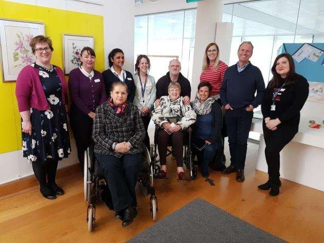 A group of St Clare Day Therapy patients, their families and staff at the exhibition