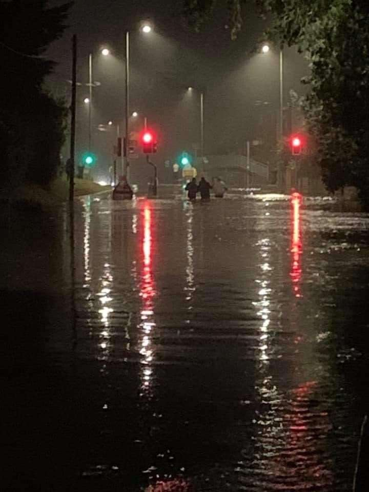 Three men NOT in a boat... Pedestrians wading through the waist-high water in Stansted Road on Thursday evening. Picture: Ami Brooking
