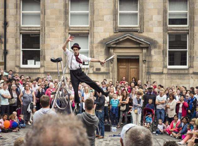 A street performer balances on a tightrope, held up by volunteers picked from the crowd on the Royal Mile, on the first weekend of the 2013 Edinburgh Festival Fringe.